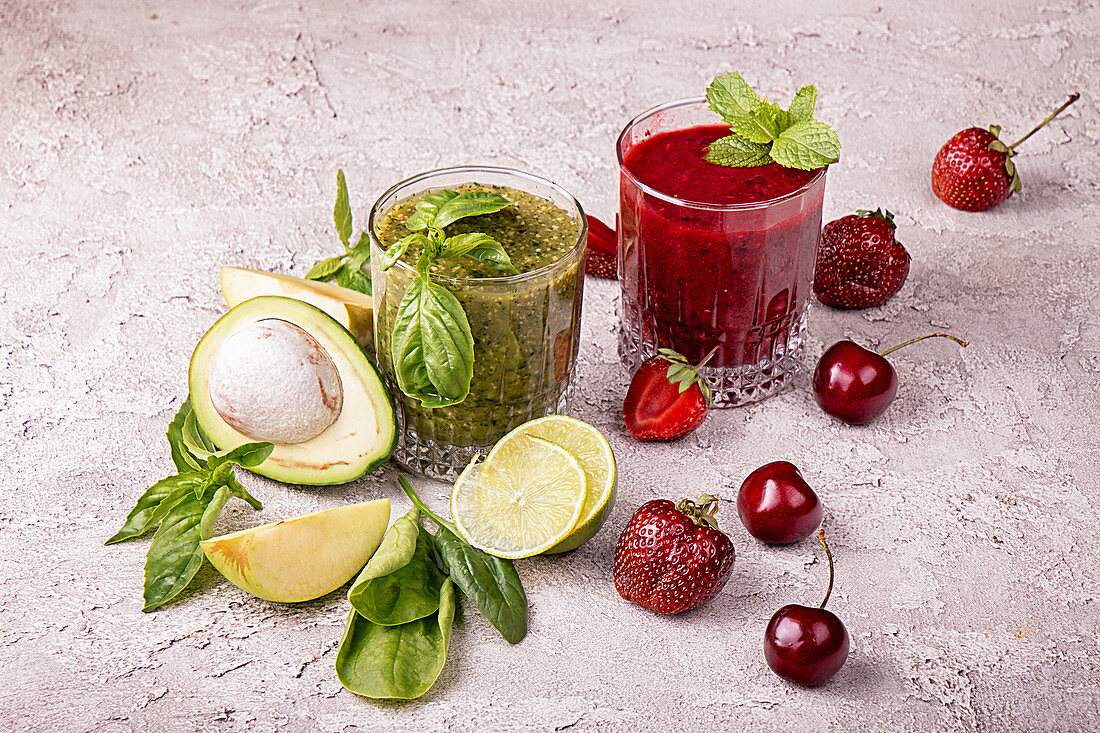 Green and red smoothie of strawberry, sweet cherry, avocado, spinach, basil, lime, green apple