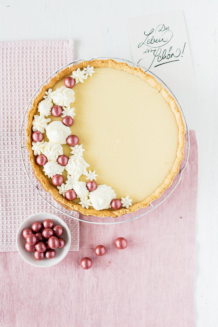 Liquorice tart decorated with liquorice balls and cream drops