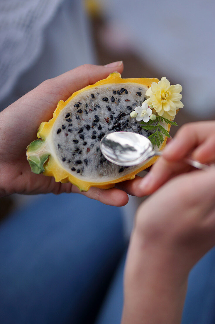 A person spooning pulp from a yellow dragon fruit