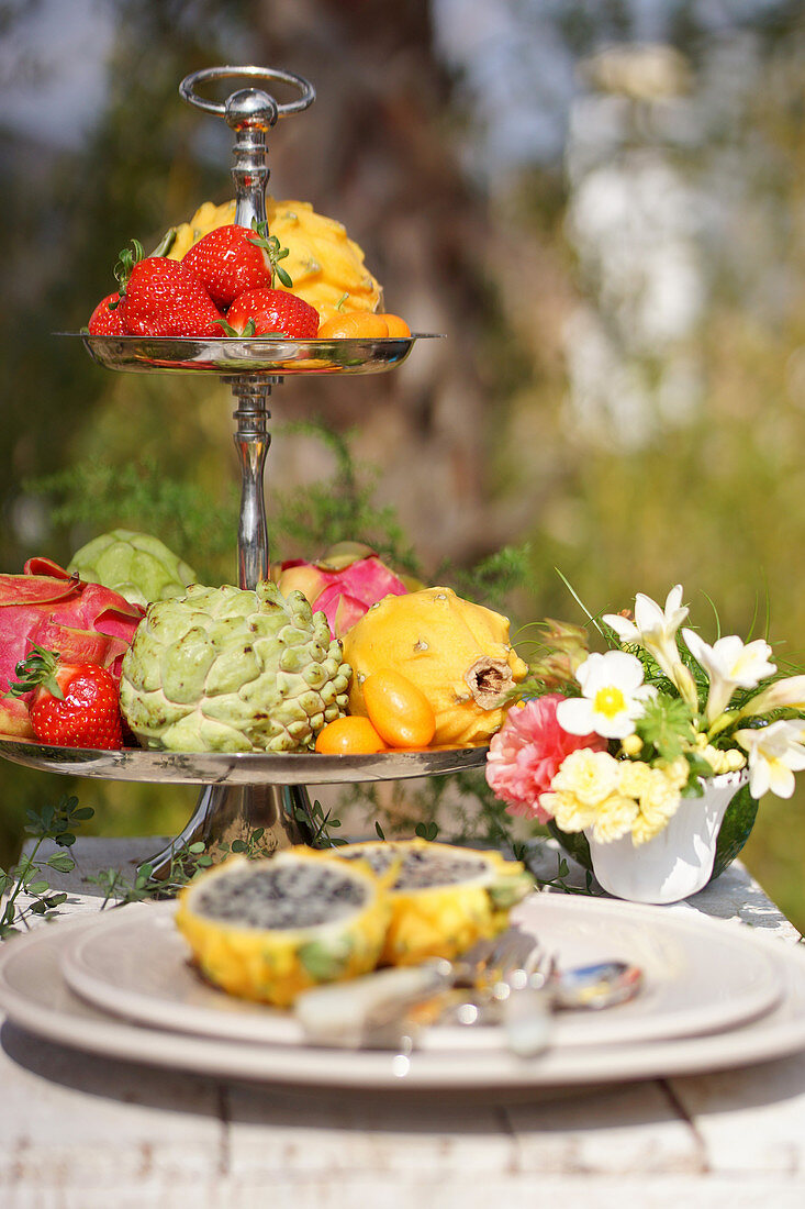A cake stand with strawberries and exotic fruits on a outdoor table