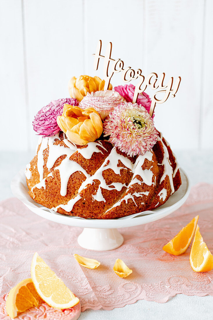 Orange gugelhupf decorated with flowers and lettering saying 'Hooray'