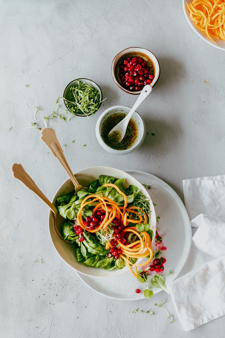 Lambs lettuce with carrot noodles and pomegranate seeds