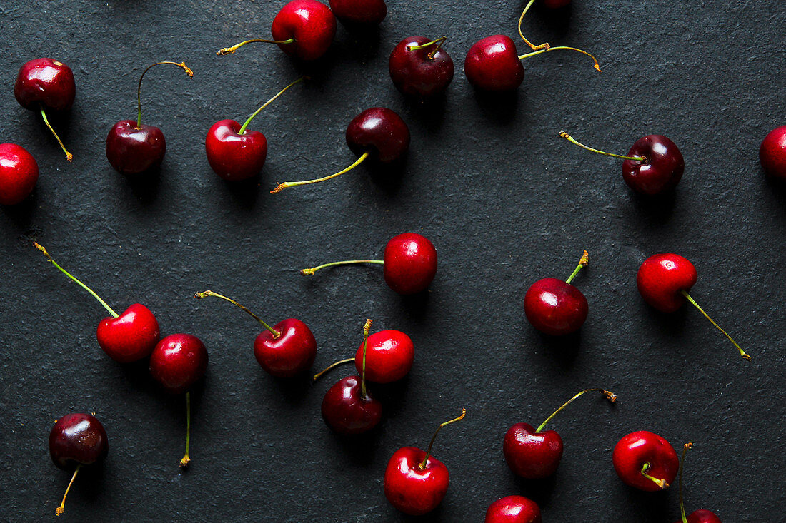 From above bright red appetizing cherries with stems on black background