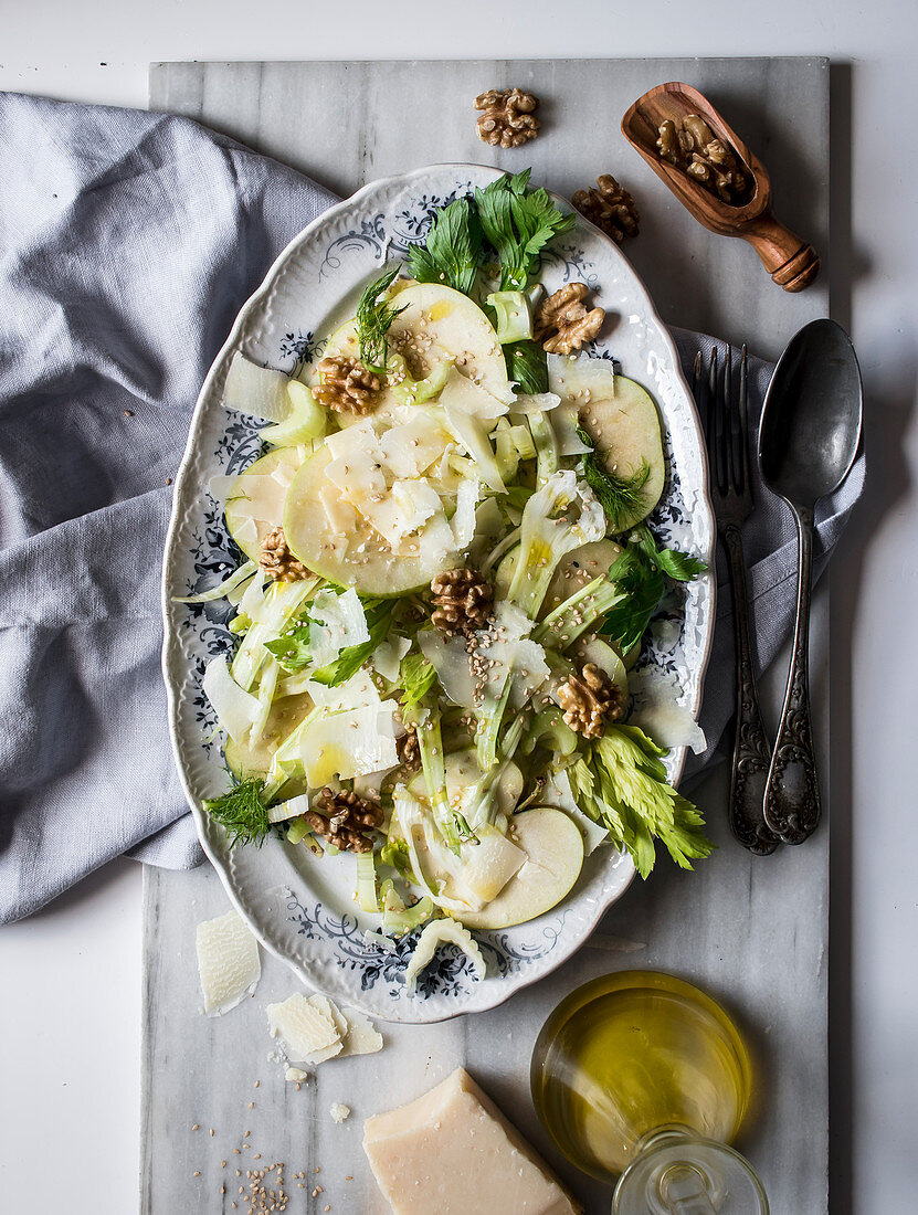 From above dish with delicious salad made of apples, parmesan cheese, walnuts, celery and oil on white background