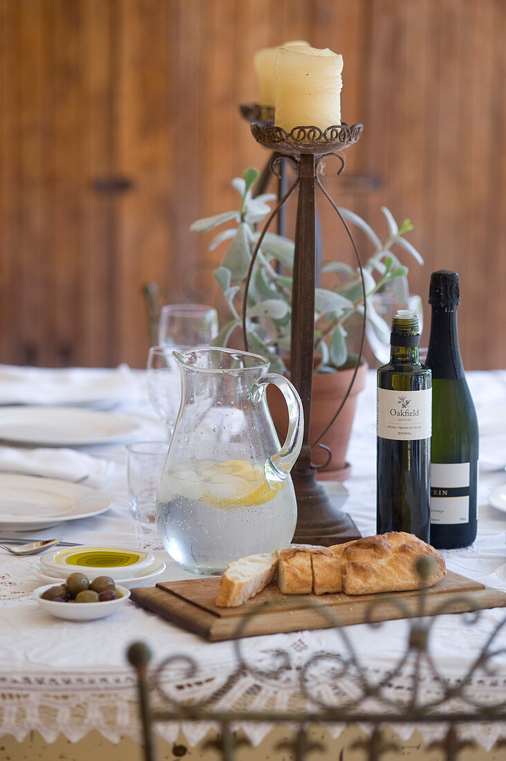 Table set with ciabatta, olives, olive oil and jug of water
