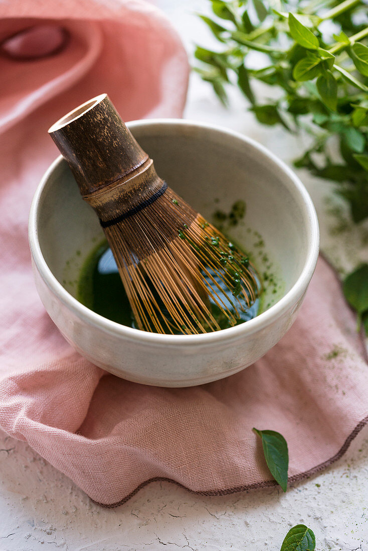 Matcha tea being stirred with a tea whisk