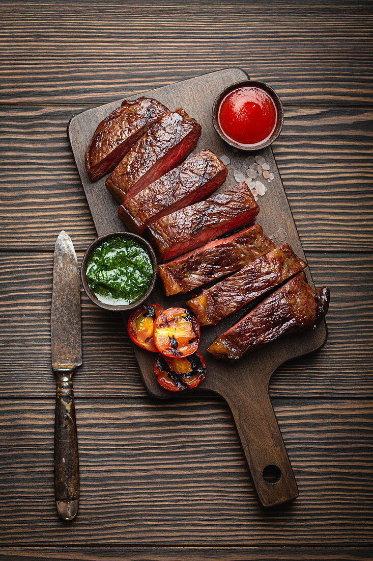 Grilled or fried and sliced marbled meat steak with fork, tomatoes as a side dish and different sauces on wooden cutting board, top view, close-up