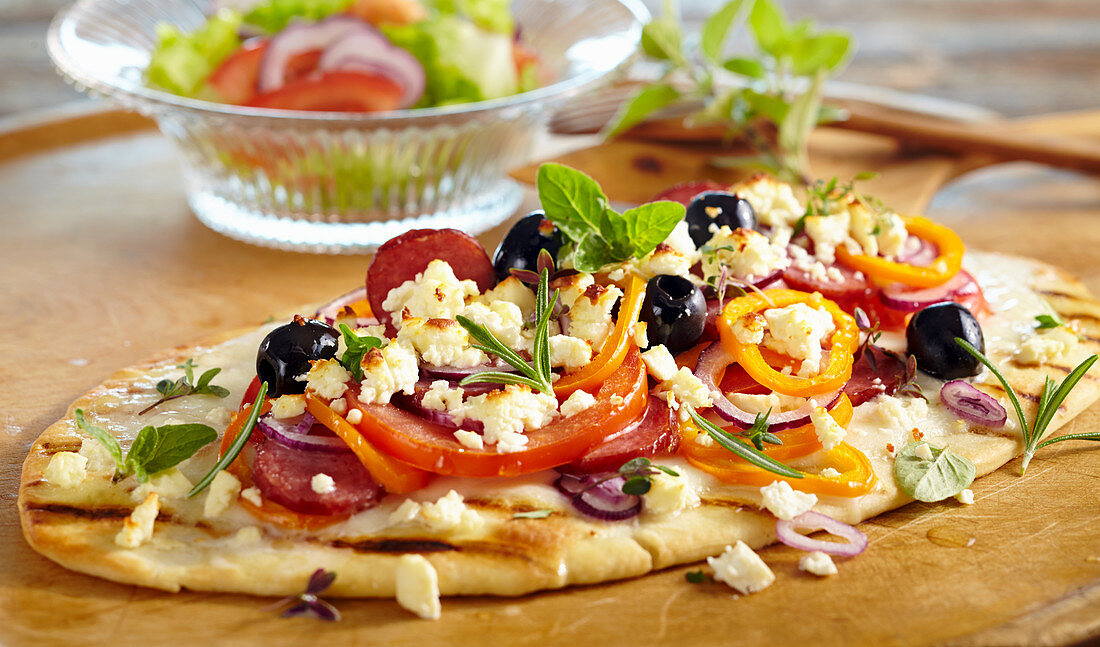 Grilled pizza topped with sausage, feta cheese, olives, peppers and fresh herbs