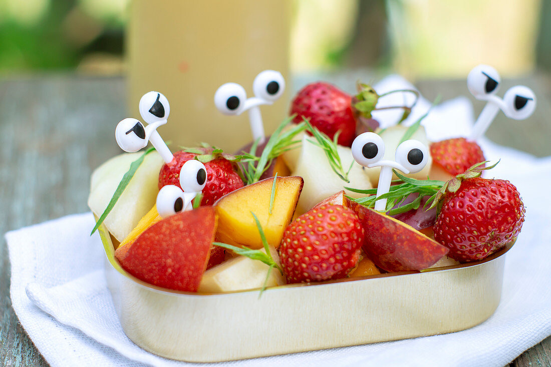 Summer fruit and berry salad in a jar with funny cartoon eyes picks