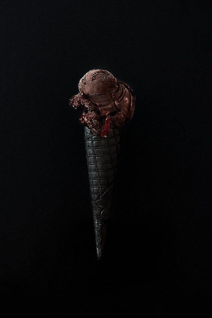 Dark chocolate with raspberry ice cream on a charcoal cone.