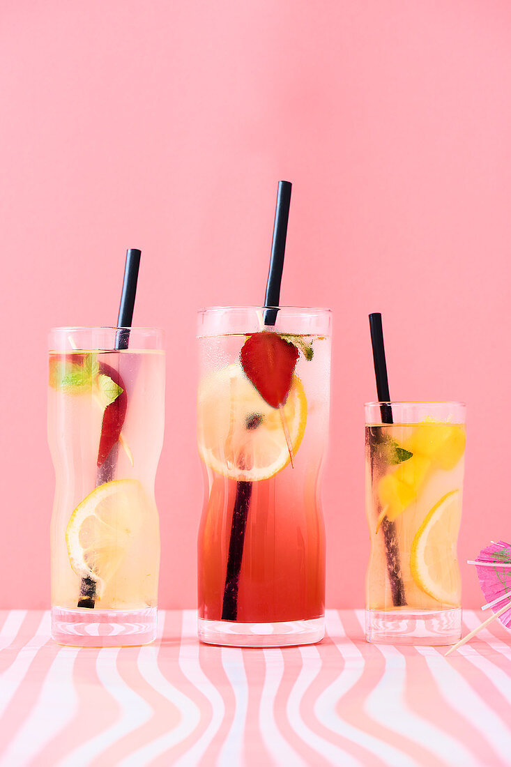 Peach, strawberry and mango lemonades with mint and lemon slices.