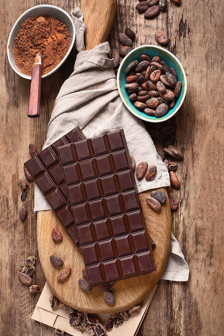 Bars of chocolate, cacao powder and cacao beans on wooden board