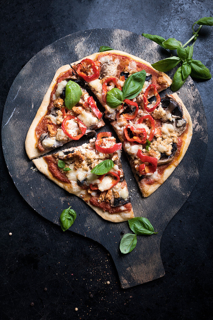 Vegan pizza with falafel, mushrooms, peppers and substitute cheese