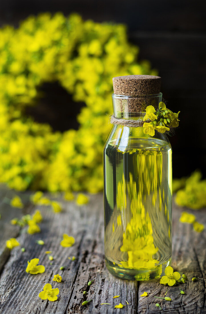 Rapeseed oil in a small bottle and rapeseed flowers