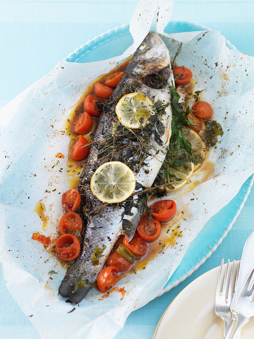 Bass with thyme, cherry tomatoes and lemon on parchment paper
