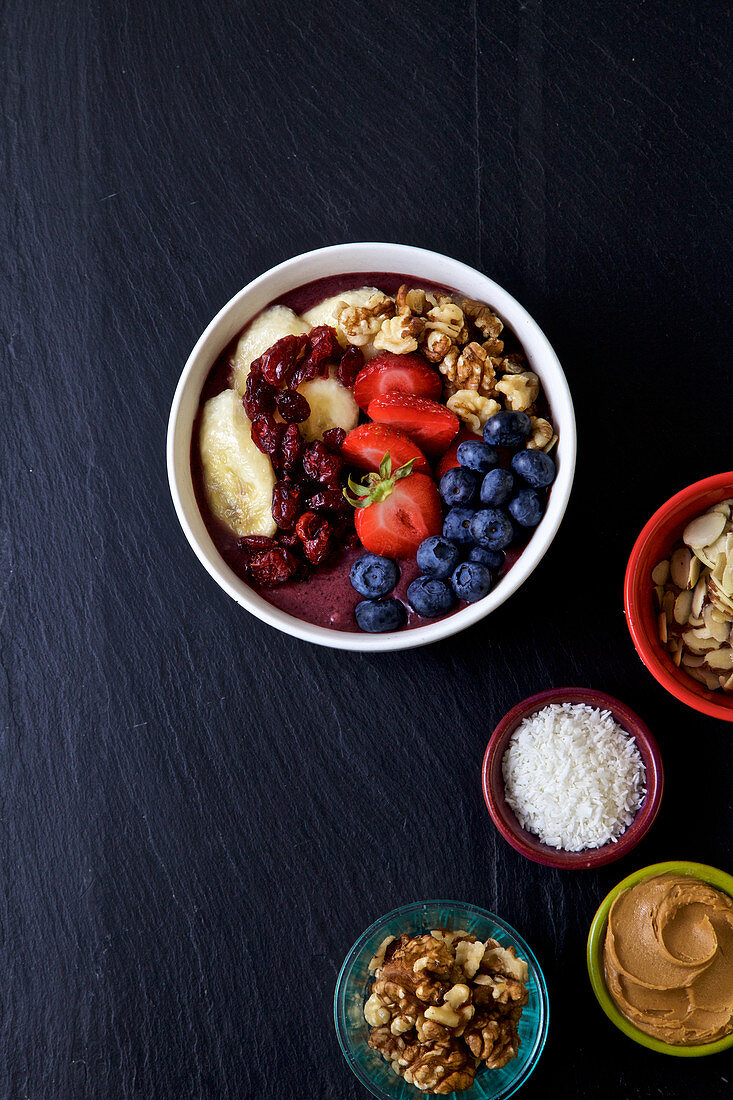 Pitaya bowl with bananas, blueberries almonds, strawberries, coconuts flakes and cranberries, peanut butter