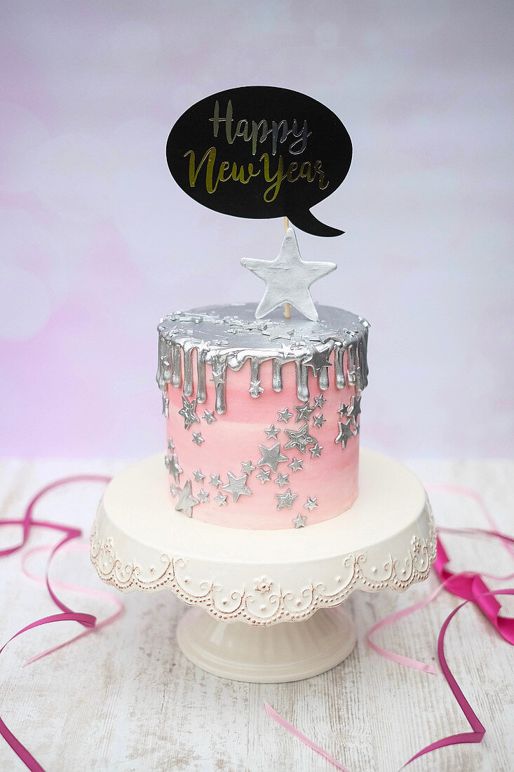 A New Year's Eve cake with sliver drips and a decorative speech bubble