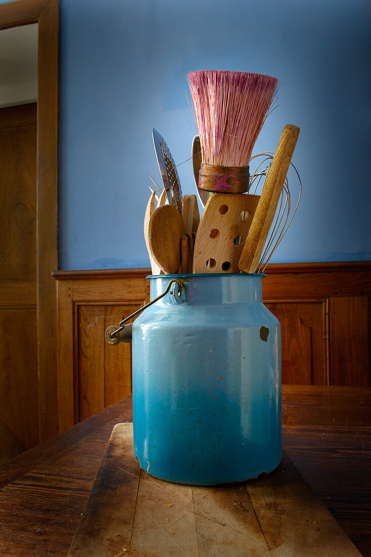 Kitchen utensils in a blue milk can on a rustic wooden table