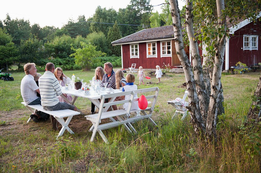 Family having meal in garden, oland, Sweden