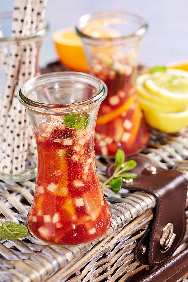Sangria made with lemons, oranges, apple, brandy and red wine in a preserving jar to take away (picnic)