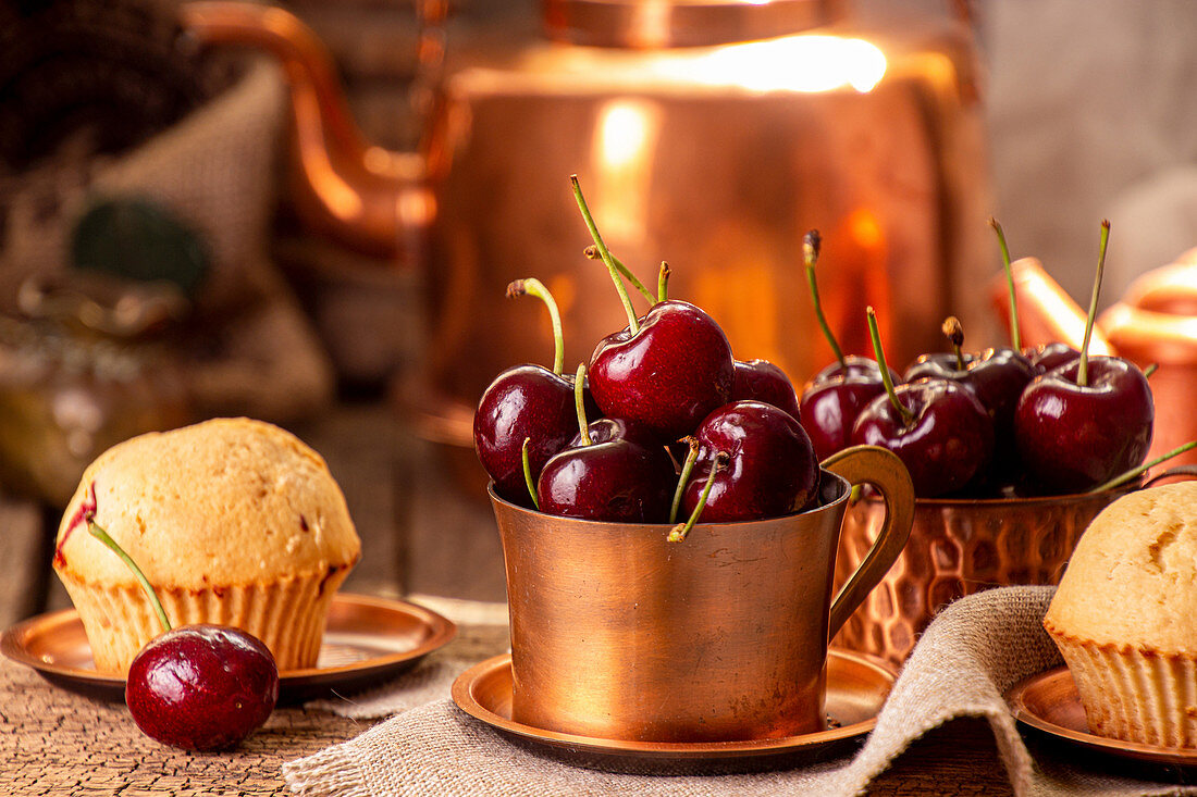 Sweet cherries in cooper cups and muffins against old vintage cooper dish