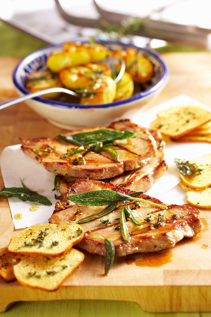 Grilled pork collar steaks with spicy grilled potatoes and sage bread chips