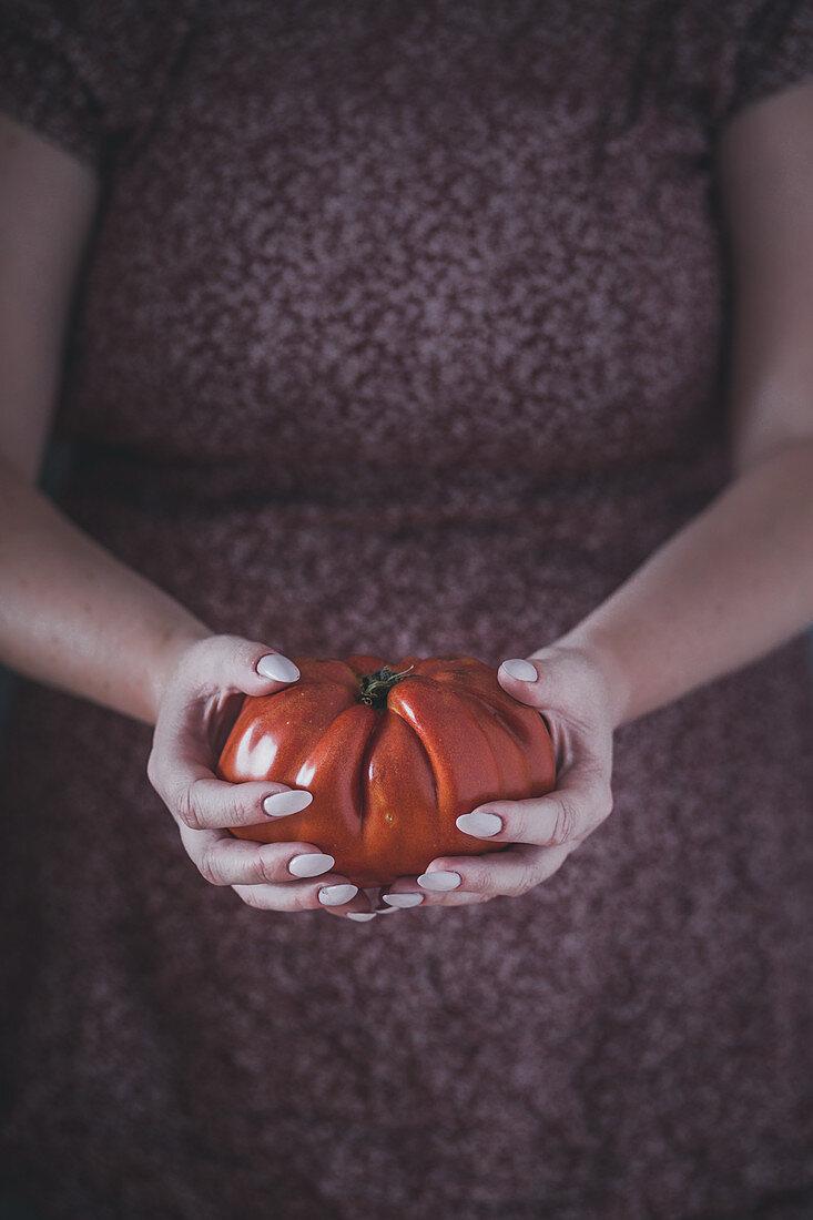 Woman holding a big tomato