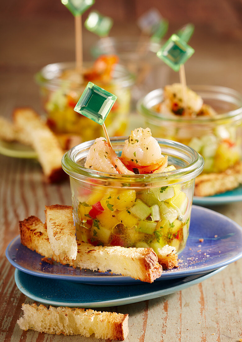 Summer party snack: mango and cucumber salad with fried shrimps and toasted bread