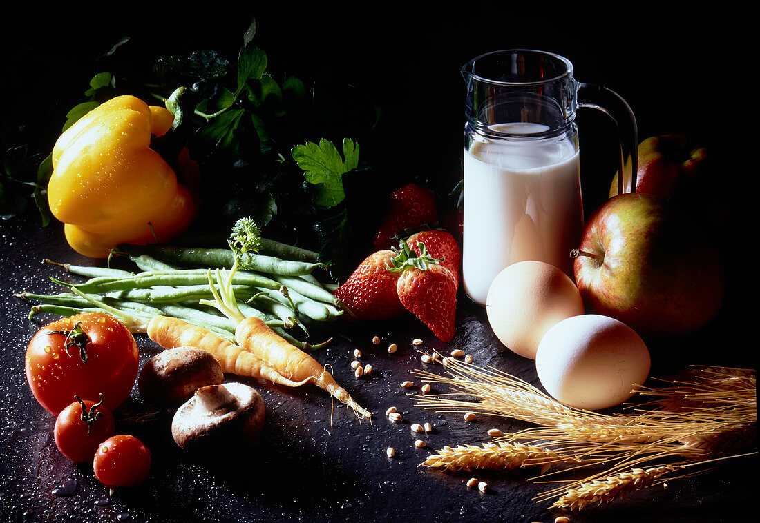 Still life with milk, eggs, fruits, vegetables, mushrooms and ears of corn