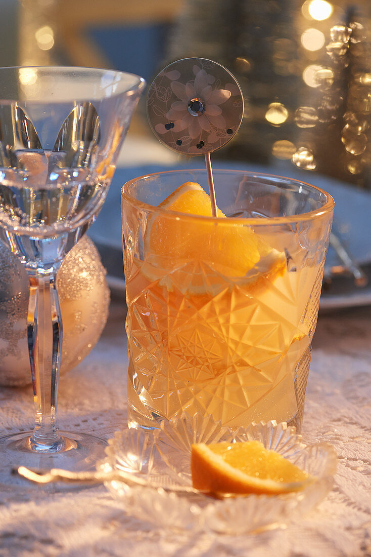 Cocktail with oranges in a cut glass on a Christmas table