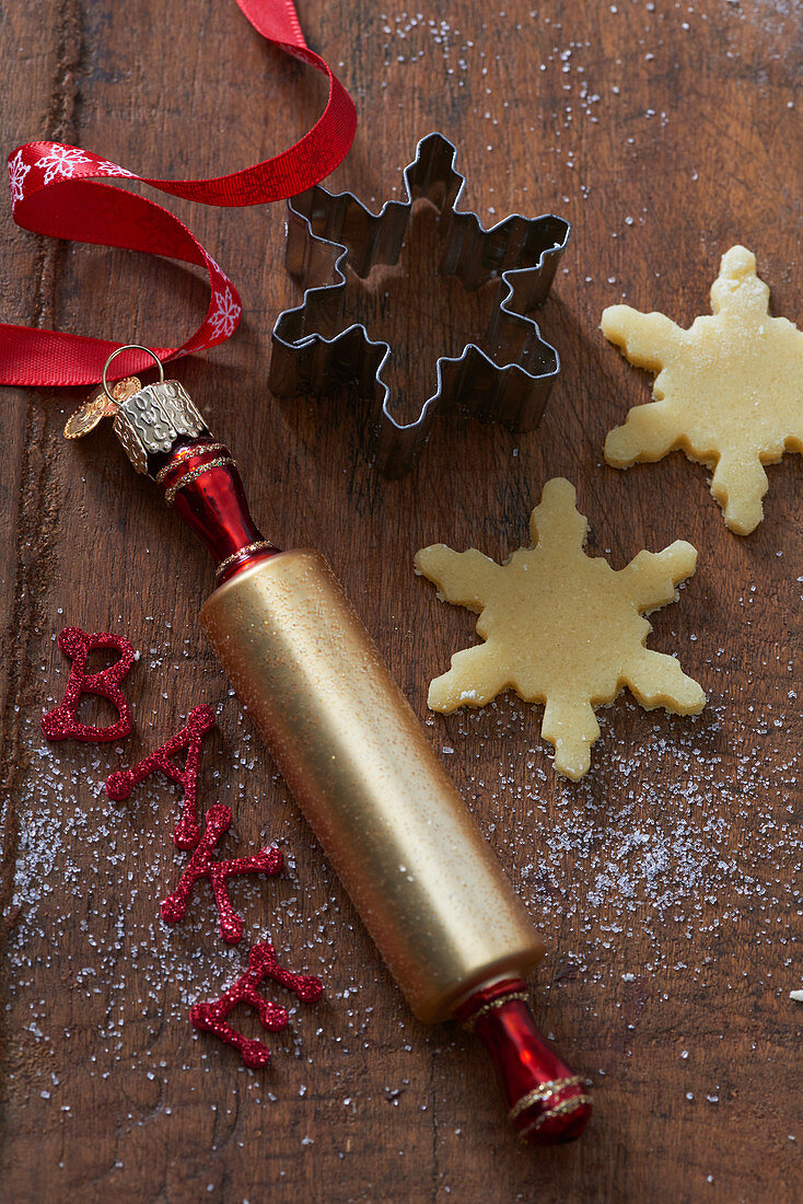 A rolling pin as a Christmas tree decoration with snowflake cookies and a cookie cutter