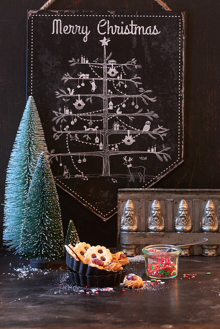 Christmas tree on chalk board, small Christmas tree ornaments, biscuits and vintage flan tins
