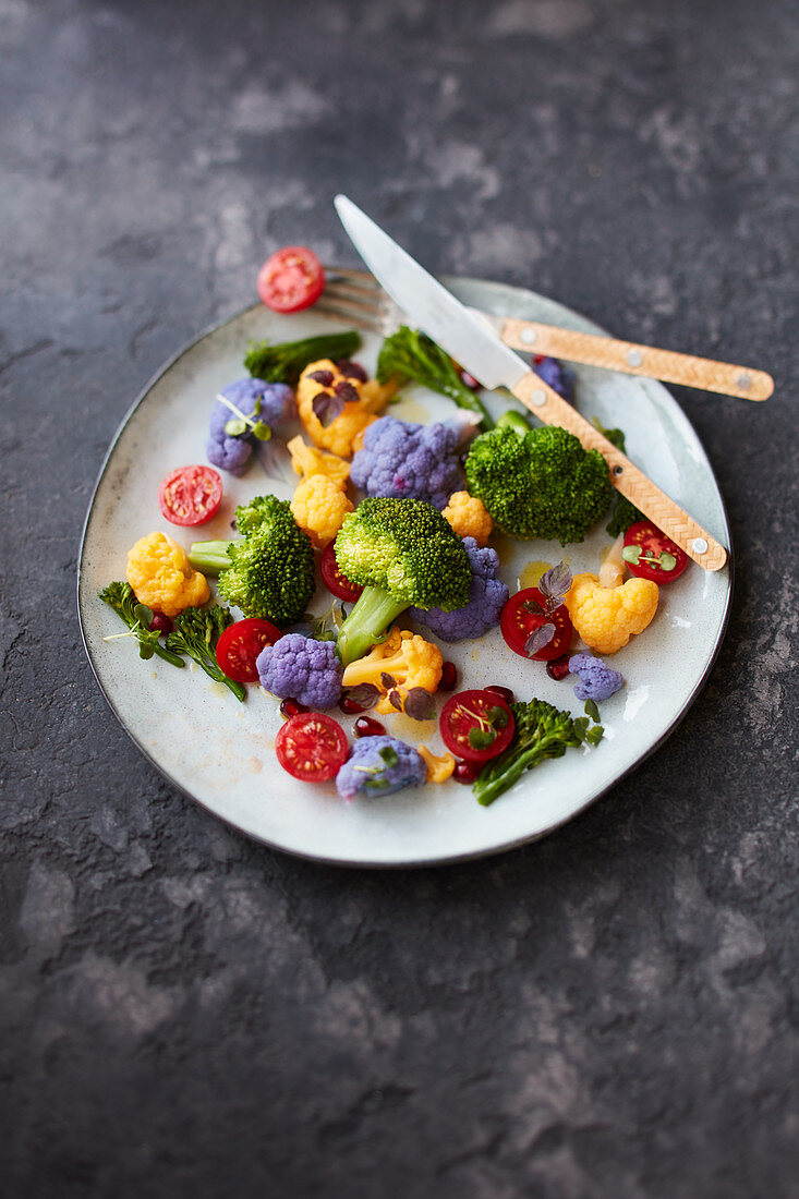 Variously brightly coloured broccoli florets with cocktail tomatoes and rape blossoms