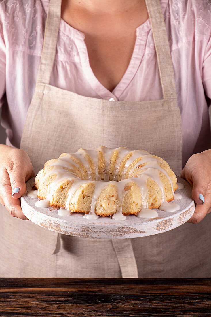 Iced sugar cake on tray in woman hands