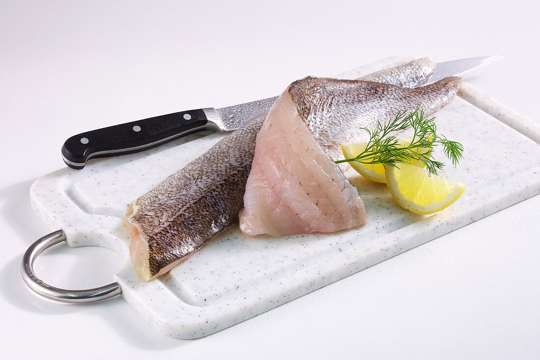 Zander fillets with skin on a board with a knife, lemon and dill
