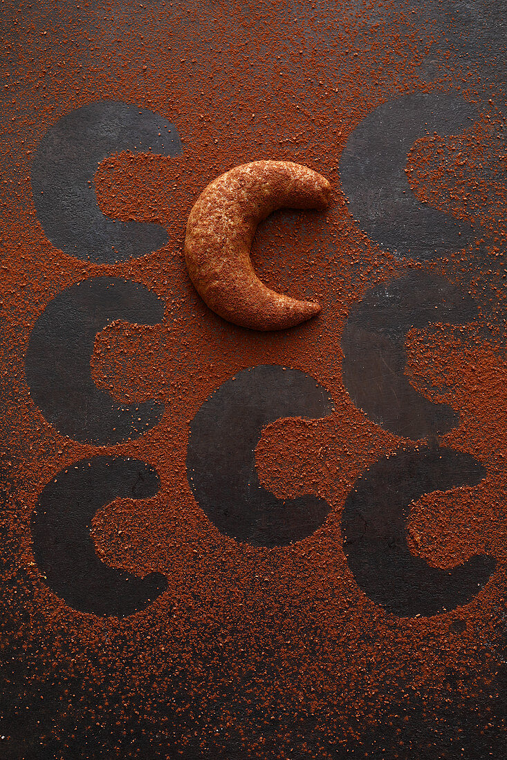 A mocha and nut crescent biscuit with cocoa powde