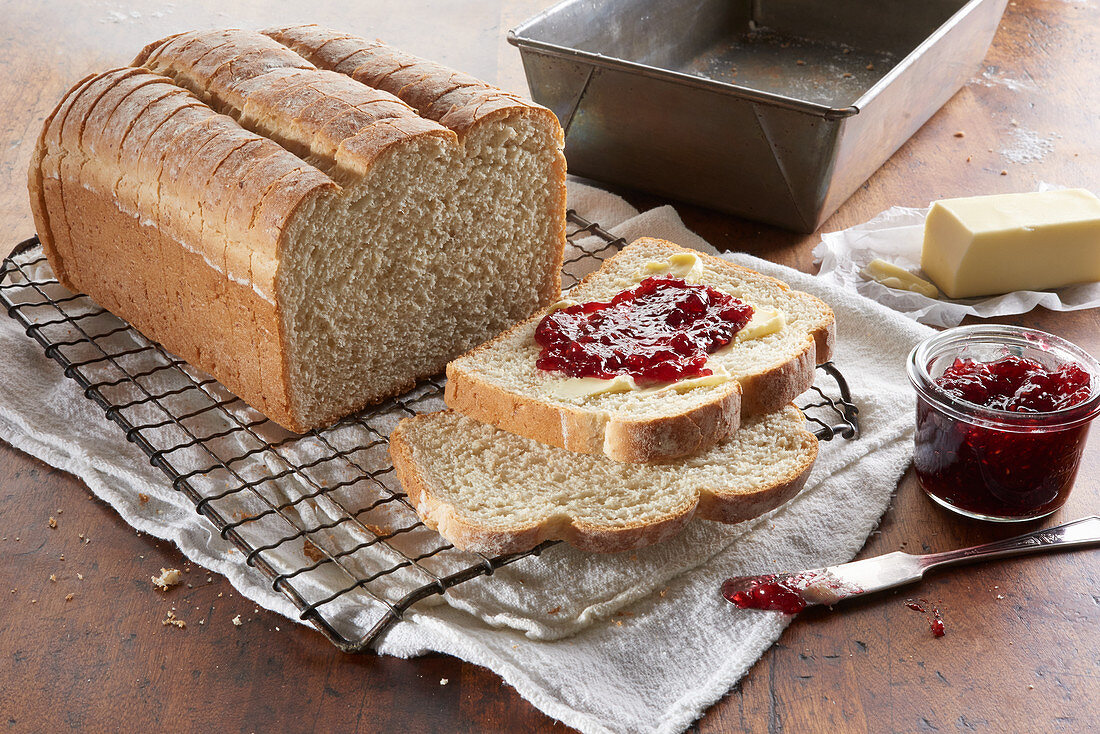 Fresh baked bread loaf, sliced and topped with butter and berry jam