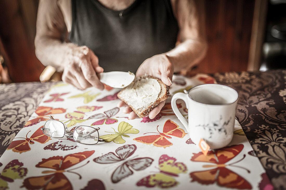 Älterer Mann isst Butterbrot und Tee zum Frühstück