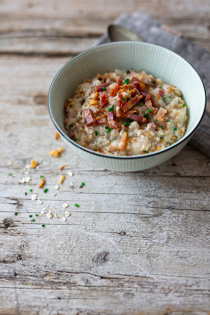 Porridge with oatmeal, bacon, fried onions and chives