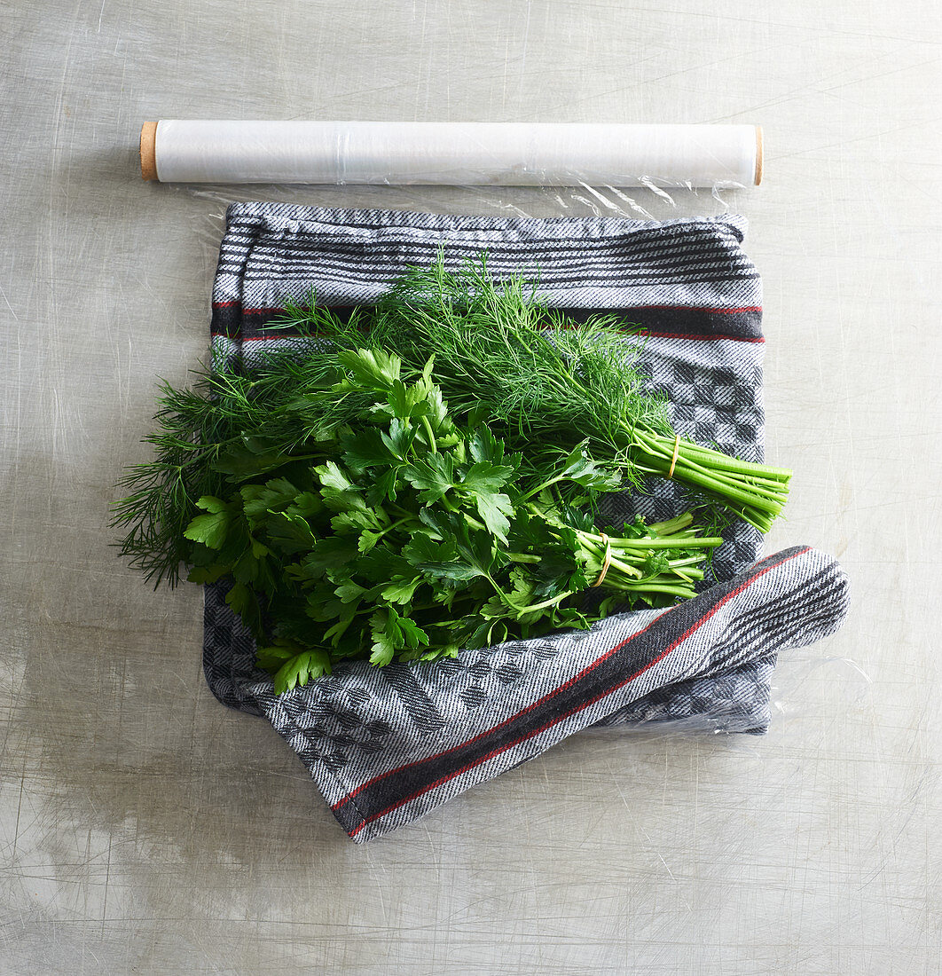 Herbs wrapped in a damp tea towel and cling film