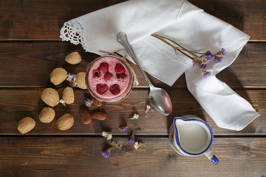 Raspberry smoothie in glass jar with almond milk