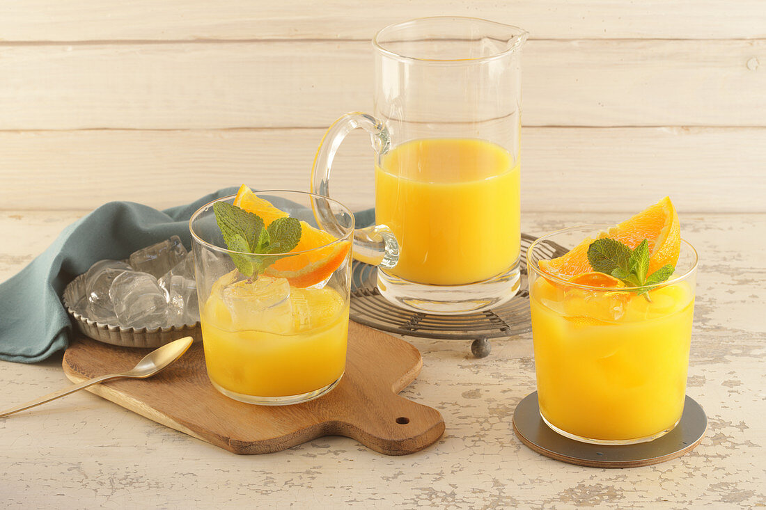 Glass and Pitcher of Orange Juice on White Background