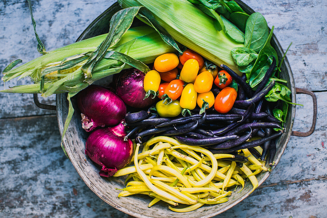 Corn on the cob, purple beans, red onion, spinach, tomato, yellow beans