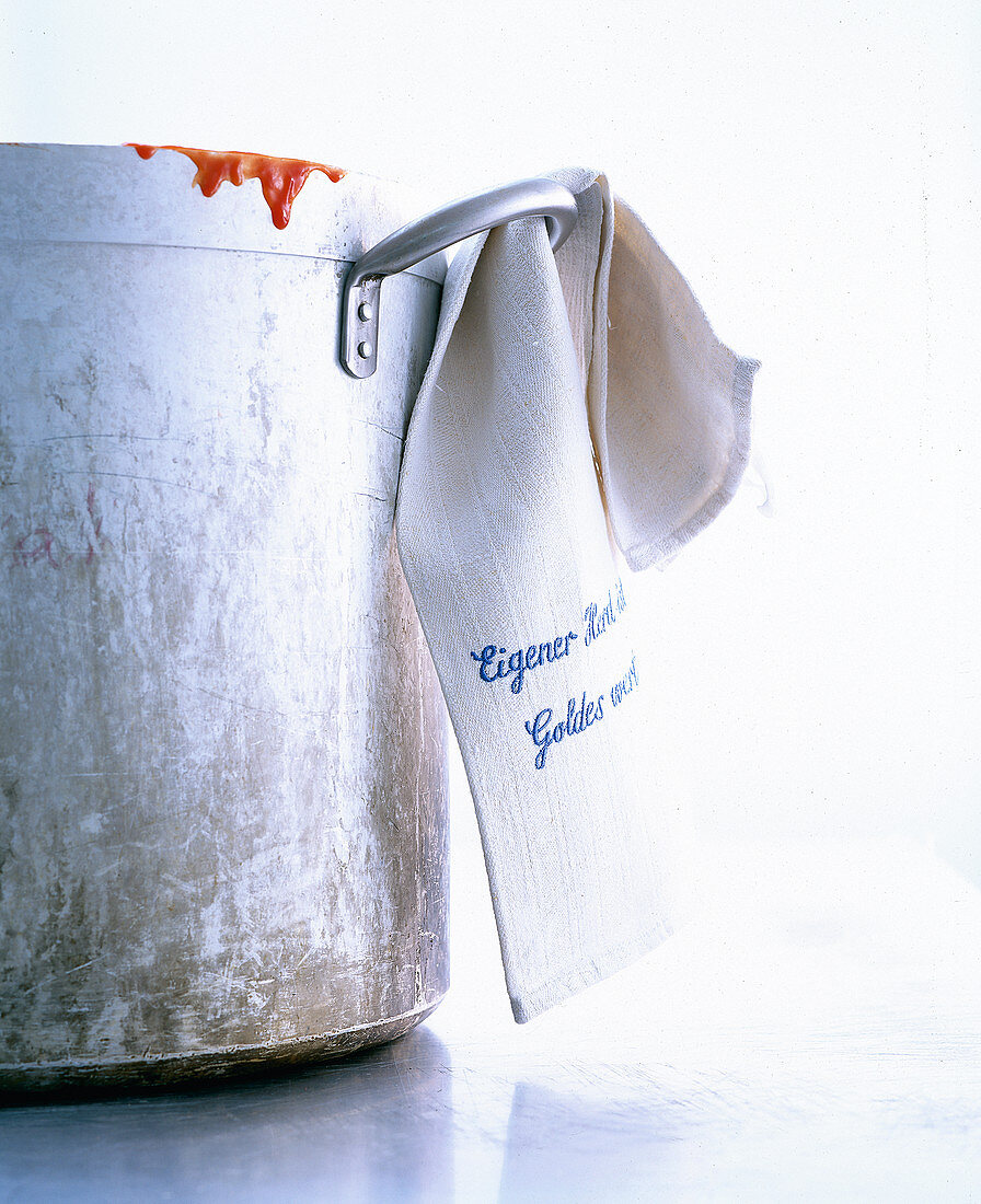 A cooking pot and tea towel with an embroidered motto