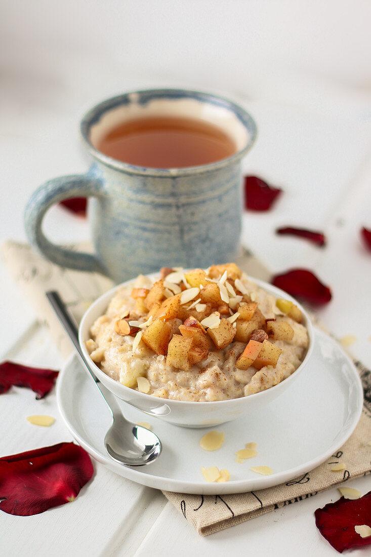 Apple cinnamon porridge with almond flakes and cup of tea