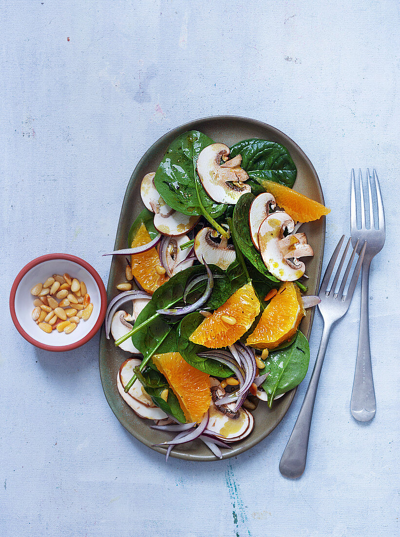 Vegan salad with baby spinach, mushrooms and orange fillets