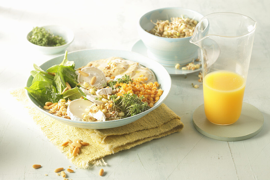 Orange lentil hummus with spinach, goat's cheese and sprouts