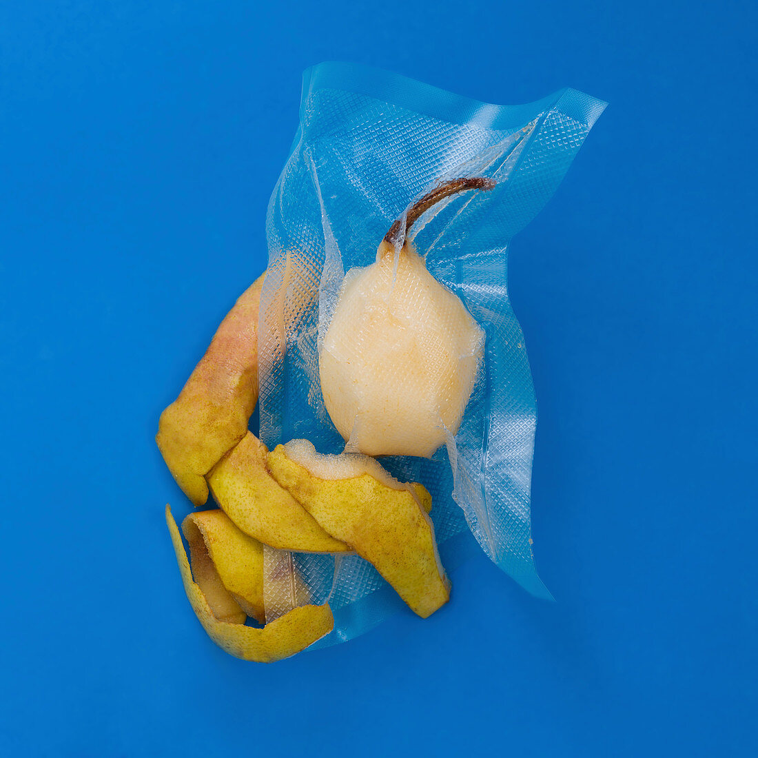 A peeled pear vacuum-packed in a plastic bag