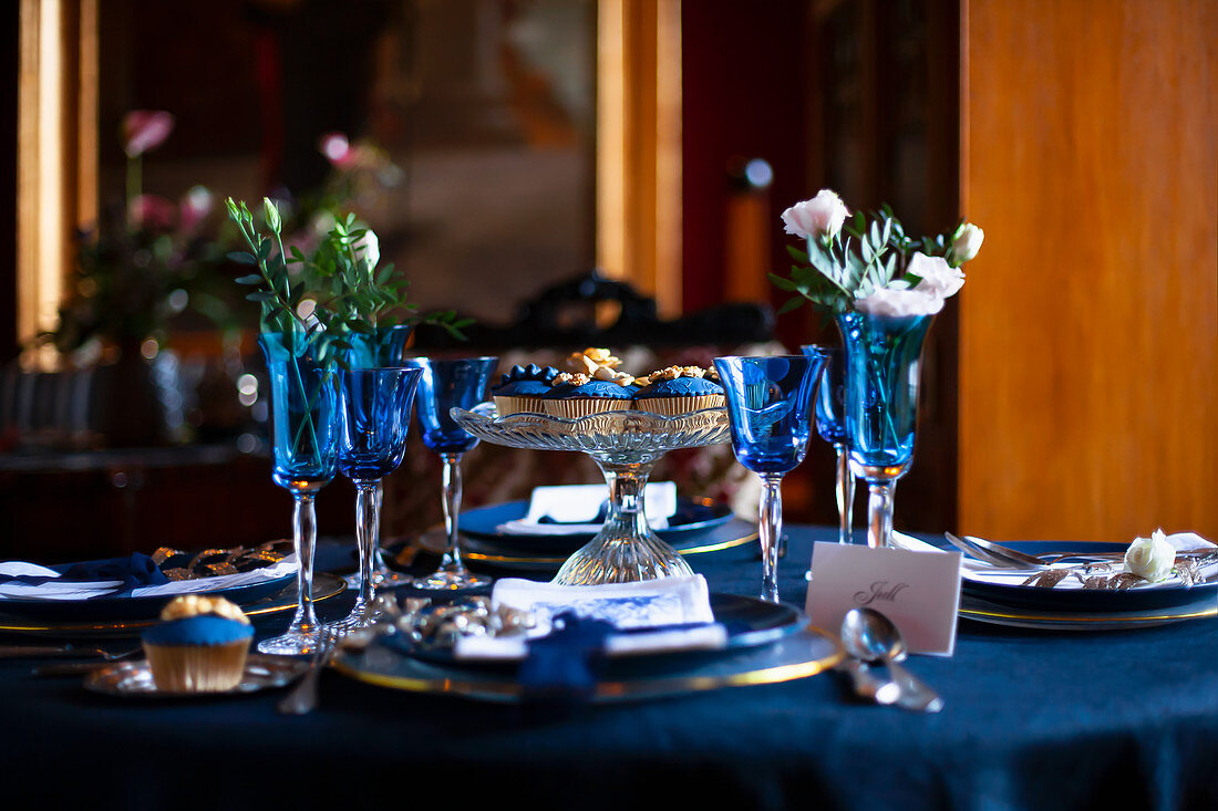 Blue glasses, plates and flowers on festively set table