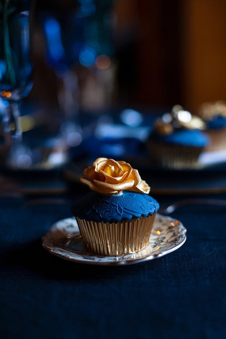 Perfekt dekorierter Cupcake mit blauem Topping und goldener Rose